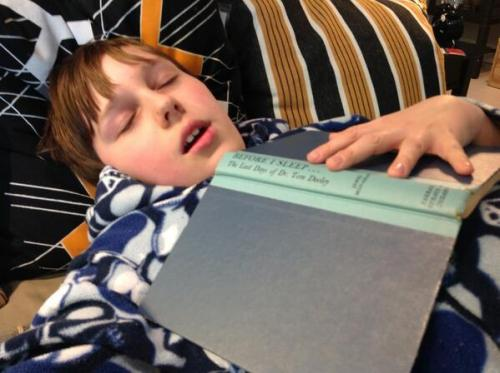 "Kid ponders ""Before I Sleep: The Last Days of Dr. Tom Dooley"" at IKEA furniture store."